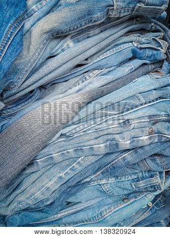 Pile of jeans of various shades, Background fashion jeans