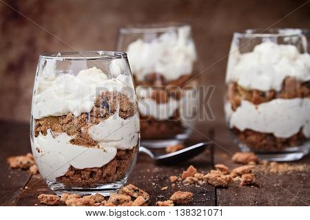 Three glasses of crumbled chocolate chip cookies and cheesecake parfaits against a rustic background. Extreme shallow depth of field with selective focus on dessert in front.