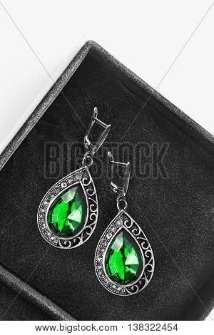 Vintage emerald earrings in black jewel box as a background