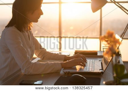 Side view photo of a female programmer using laptop, working, typing, surfing the internet at workplace