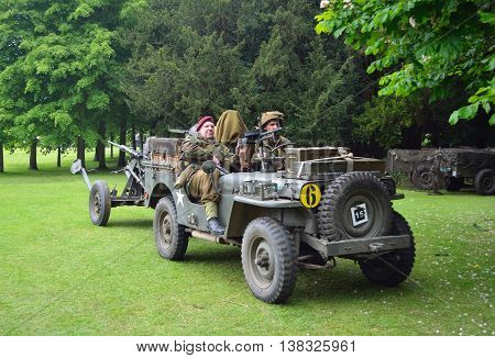 Silsoe, Bedfordshire, England - May 30, 2016: World War 2 Jeep with men dressed as World War 2 Soldiers, towing Gun.