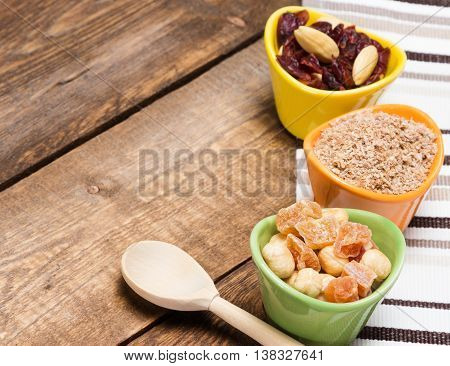 Healthy eating background. Wooden spoon and ceramic cups filled with wheat bran mixtures of nuts with dried fruits and berries. Peeled hazelnut, almond, papaya, cranberries