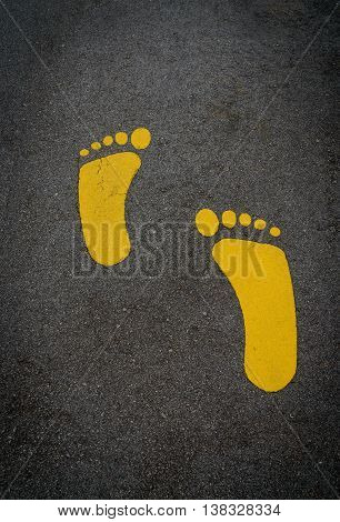 Yellow footprint on an asphalt road  in Singapore.