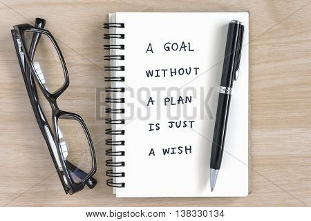 a goal without a plan is just a wish motivational handwriting on a notebook with pen and eye glasses on the desk