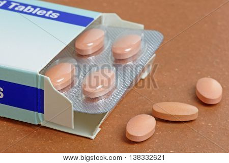 Statins or generic pills pouring from a pack. Close up with shallow depth of field