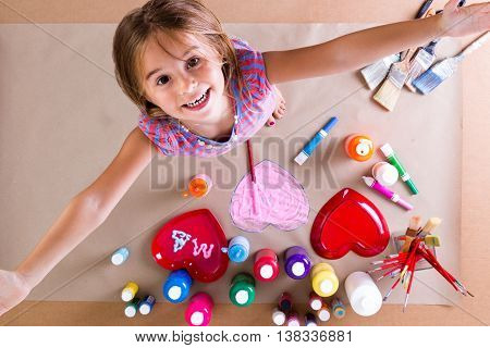 Happy creative little girl with her paints and brushes standing looking up at the camera with her arms outstretched and a beaming smile as she shows the breadth of her vision