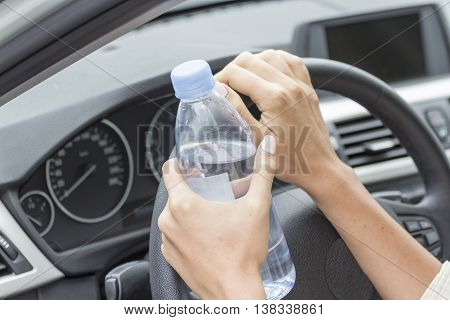 Girls hold hands a bottle of clean fresh drinking water in the car.
