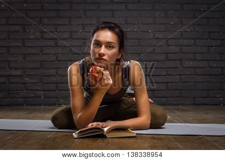 Beautiful Girl Doing Yoga Exercises And Read Book On Brick Wall Background