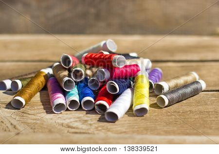 thread reels on wooden background and different color