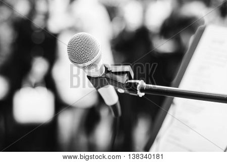 A microphone on a stand among the crowd. Black and white photo.