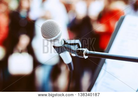 A microphone on a stand among the colorful crowd.