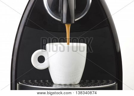 machine serving espresso coffee in a glass cup