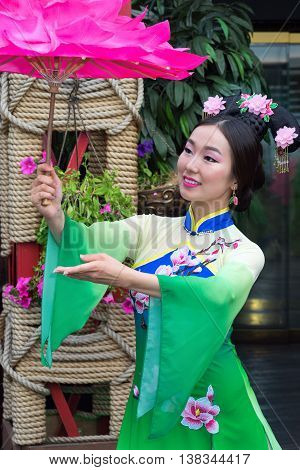 Chinese girl in a traditional dress with floral parasol