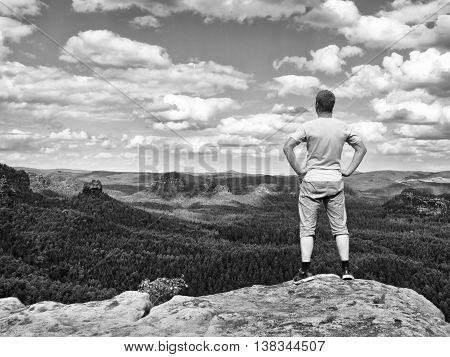 Man In Trekking Shorts On Cliff Of Rock Empire Watch