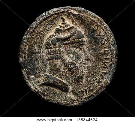 Ancient coin with head isolated on black top view