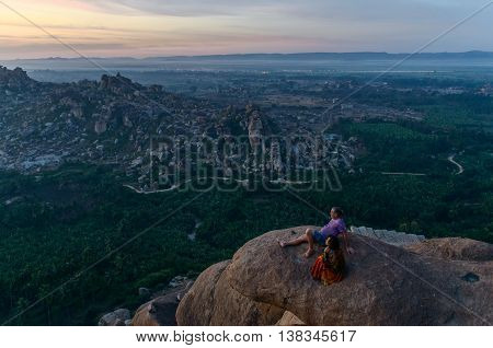HAMPI KARNATAKA INDIA - FEBRUARY 02 2016: People waiting for sunrise at the top of viewpoint of Hampi