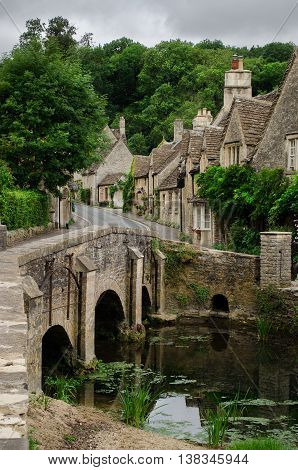 Castle Combe village in the Cotswolds in a vertical shot with the bridge and the High Street with the typical honey-coloured limestone houses in England.