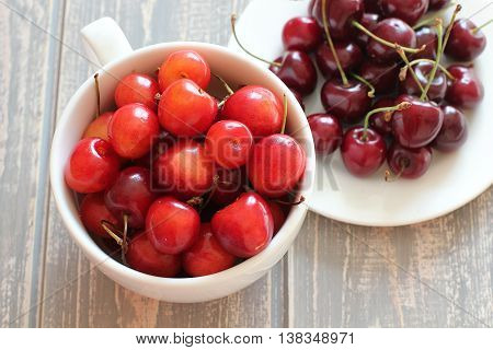 Cherries in white cup on wooden grey desk. Stock photo.