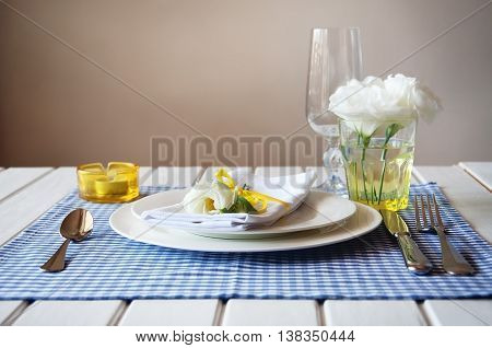 Table setting with blue checkered tablecloth white napkin silverware yellow decoration and flowers