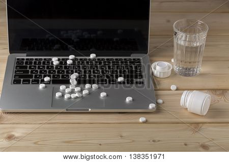 Set from scattered white round pills on the laptop keyboard