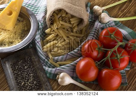 Pasta, tomatoes, garlic and grated cheese on wooden background.