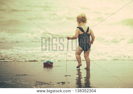 little baby girl laughing on the beach in the water. shu's playing with a toy boat. she's wearing an adorable flower swimsuit. with a retro look