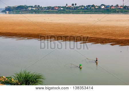 Vientiane Laos - March 15 2013: Locals fish with traditional nets in Mekong River Vientiane Laos