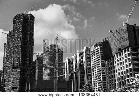 Black and white photo of unfinished skyscrapers.