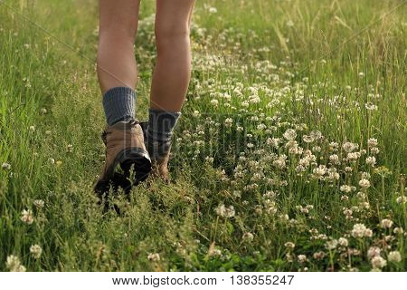 young woman hiker legs walking on trail in grassland