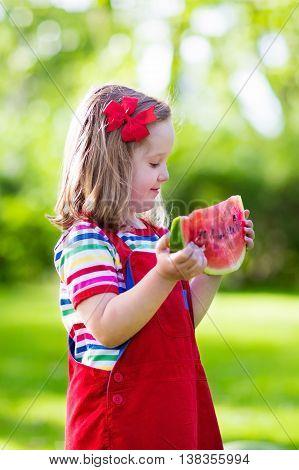 Little Girl Eating Watermelon In The Garden