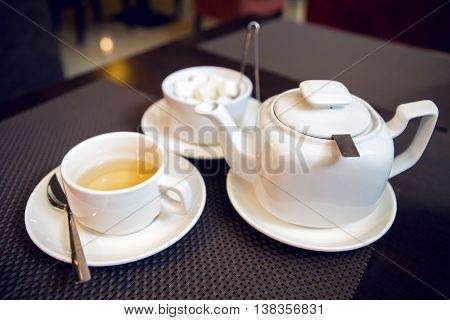 white teapot with tea Cup, saucer and teaspoon, a sugar bowl are on the table