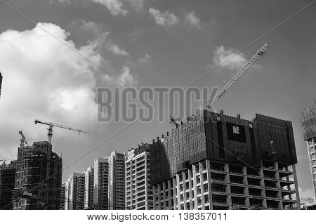 Black and white photo of construction on the background of sky.
