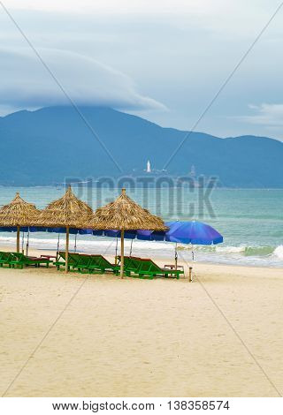 Palm Shelter And Umbrellas With Sunbeds In China Beach