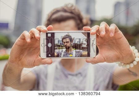 Portrait of a young man who makes selfie on the background of the city. He looks into the camera and selfie ape.