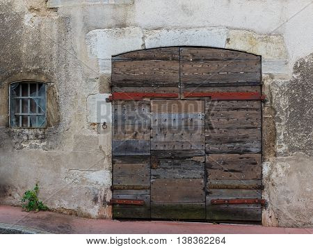 Facade of an old building with wooden gate and with a broken window. Burgundy France