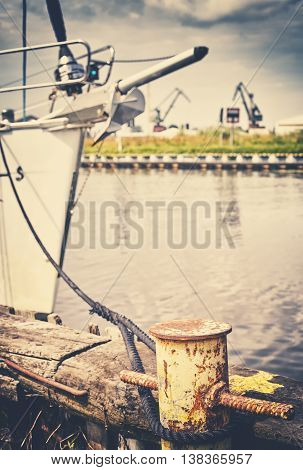 Retro Toned Yellow Bollard With Moored Sailboat.