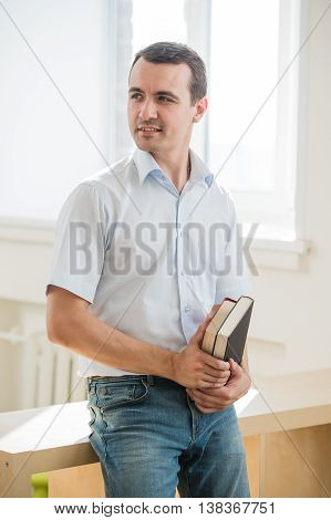 Portrait of young man holding books, looking sideways.