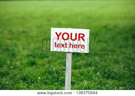 your text here sign against green lawn background