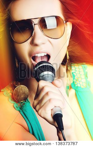 Beautiful popstar woman singing into microphone