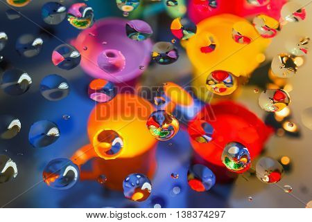 Bright colorful abstract background - view through glass with drops of water on a blurry bailers and buckets. Selective focus on foreground.