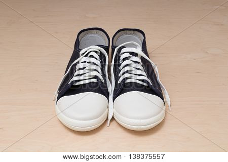 New keds with white laces on light wooden background