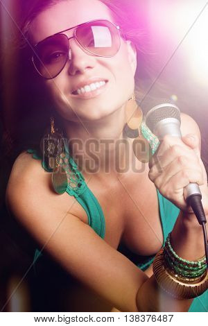 Beautiful pop star girl singing with microphone