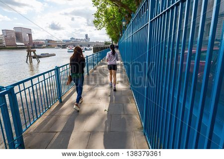 People Strolling And Jogging Along The River Thames In London, Uk