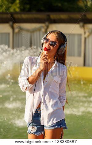 Girl listening to music on headphones. Girl in sunglasses. She licks a lollipop.