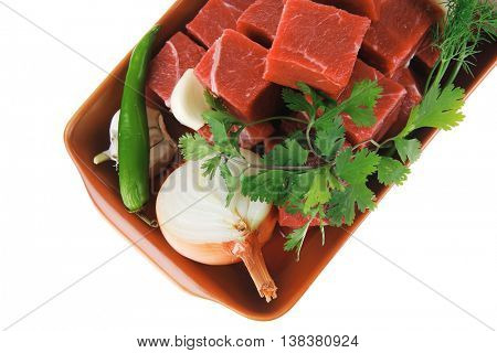 fresh uncooked beef meat slices over ceramic bowls ready to prepare with garlic and greenery isolated over white background