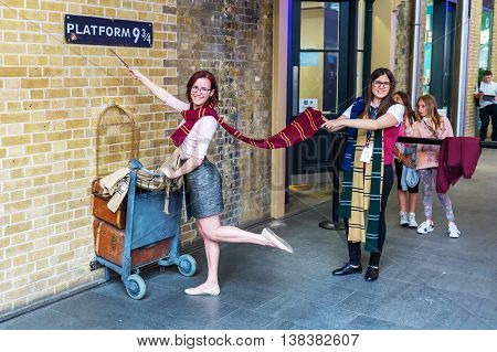 London UK - June 16 2016: Platform 9 three-quarter at Kings Cross Station with unidentified people. The platform is a fictive one from Harry Potter movies installed at Kings Cross for tourists