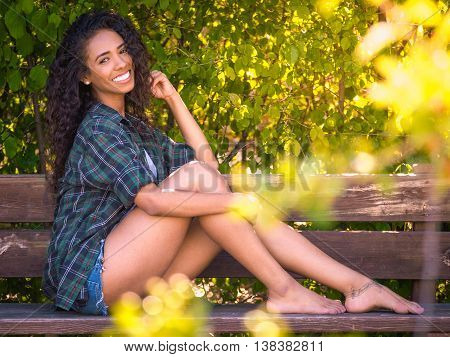 latina brunette young woman with perfect smile sitting barefoot on a bench in a park with vegetation behind