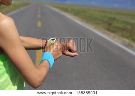 young woman runner ready to run set and looking at sports smart watch checking performance or heart rate pulse trace. sport and fitness outdoors .