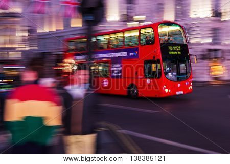 Red Double Decker Bus In Motion Blur At Piccadilly Circus In London, Uk, At Night