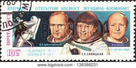 MOSCOW RUSSIA - DECEMBER 2015: a post stamp printed the USSR shows portraits of spacemen V.A. Dzhanibekov S.E. Savitskaya I.P. Volk the series
